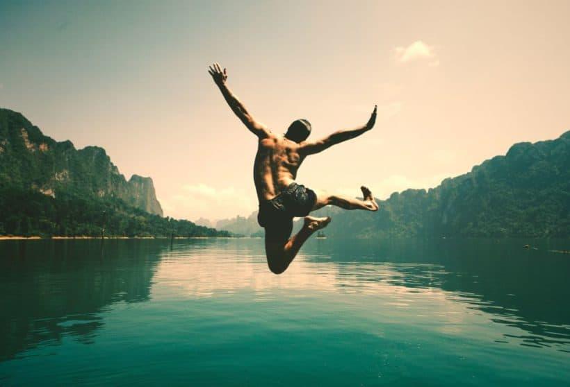Ein Mann springt in einen See und freut sich, dieses Freiheitsgefühl mit den Konzepten Minimalismus und vegane Ernährung von richKind spüren.